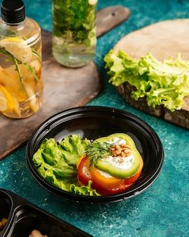 Bovenaanzicht dieet voedsel multi-gekleurde paprika op sla met walnoot en detox water