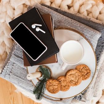 Bovenaanzicht dienblad met cookied en melk en stapel boeken