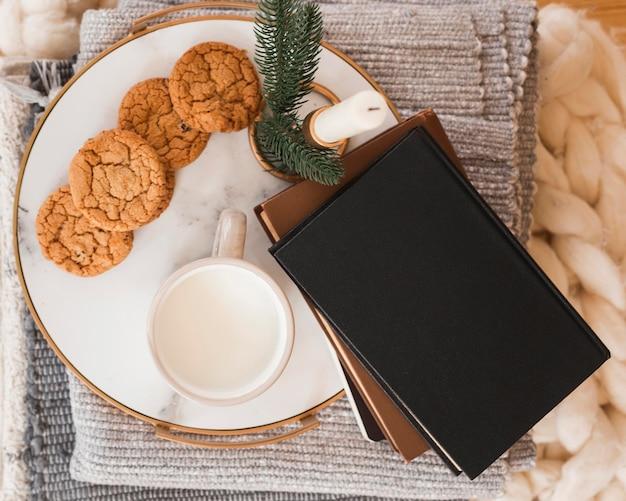 Bovenaanzicht dienblad met koekjes, melk en boeken