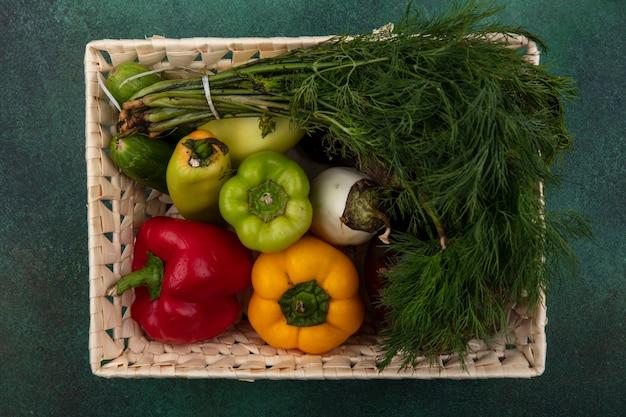 Bovenaanzicht dille met paprika en komkommers in een mand op een groene achtergrond
