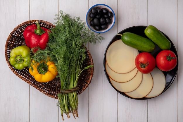 Bovenaanzicht dille met paprika in een mand met gerookte kaastomaten en komkommers met olijven op een witte achtergrond