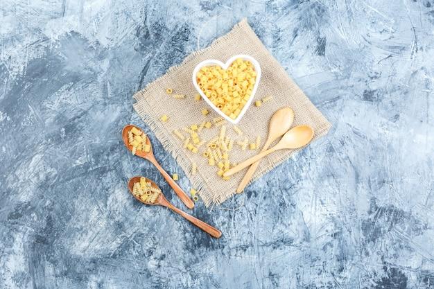 Bovenaanzicht ditalini pasta in kom met houten lepels op gips en stuk zak achtergrond. horizontaal