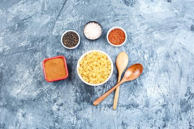 Bovenaanzicht ditalini pasta in witte kom met houten lepels, kruiden op grijze gips achtergrond. horizontaal