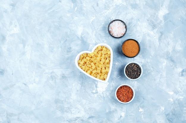 Bovenaanzicht ditalini pasta in witte kom met kruiden op grungy grijze achtergrond. horizontaal