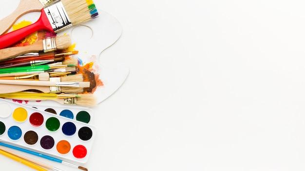 Bovenaanzicht diverse penselen met kleurenpalet