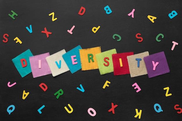 Bovenaanzicht diversiteit woord gemaakt van kleurrijke kaarten op zwarte achtergrond