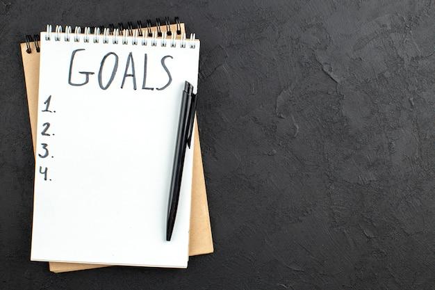 Bovenaanzicht doelen geschreven op spiraal notitieblok zwarte pen op zwart met vrije ruimte