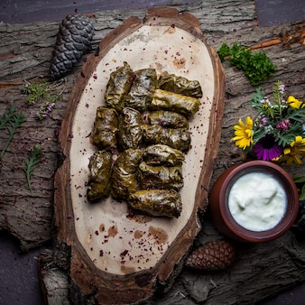 Bovenaanzicht dolma druivenbladeren gevuld met vlees en rijst met zure roomsaus. oost-europese en aziatische traditionele keuken