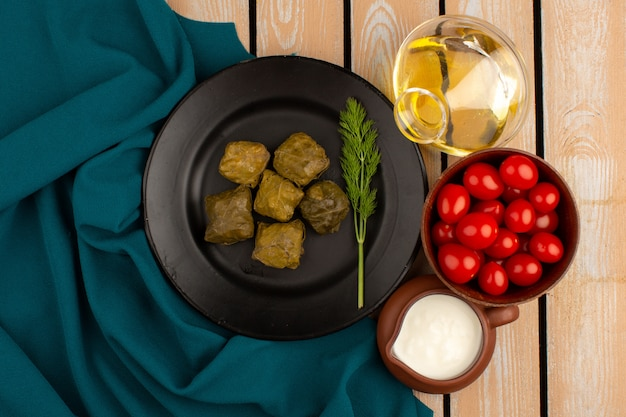 Bovenaanzicht dolma groen samen met olijfolie en yoghurt op de houten vloer