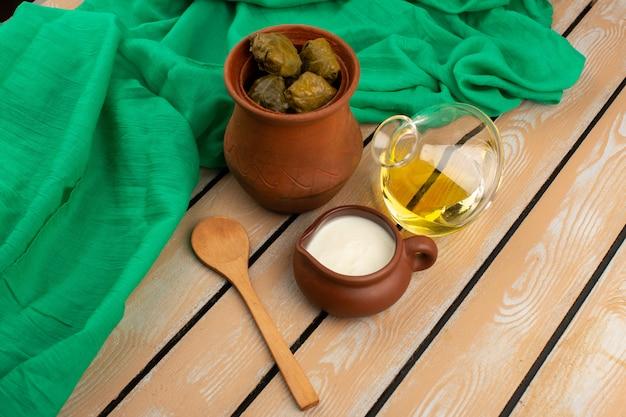 Bovenaanzicht dolma in bruine pot samen met olijfolie en yoghurt op de houten rustieke vloer
