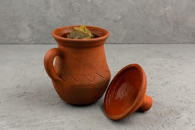 Bovenaanzicht dolma in pot groene beroemde oost-vlees maaltijd in bruine pot op de grijze