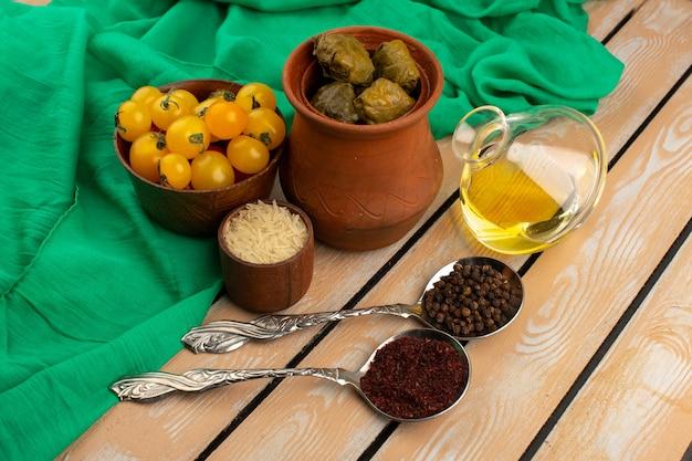 Bovenaanzicht dolma in pot samen met gele tomaten en olijfolie op de houten vloer