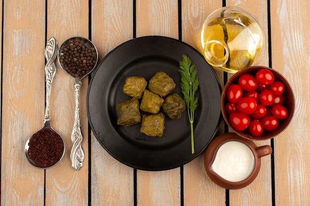 Bovenaanzicht dolma in zwarte plaat samen met rode tomaten, yoghurt en olijfolie op de houten vloer