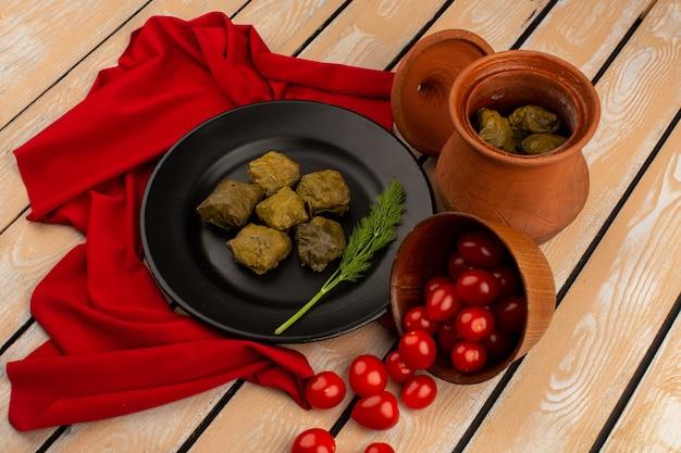 Bovenaanzicht dolma in zwarte plaat samen met tomaten en groenen op het houten bureau