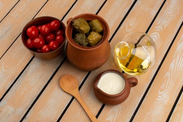 Bovenaanzicht dolma samen met rode tomaten, olijfolie en yoghurt op het rustieke houten bureau