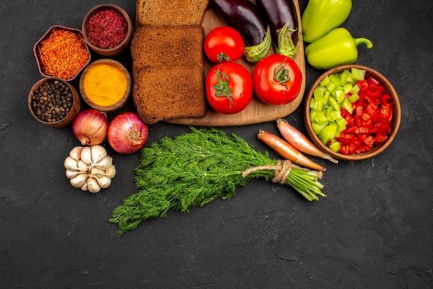 Bovenaanzicht donkere broodbroden met kruiden, groenten en fruit op een donkere achtergrond schotel salade gezondheidsmaaltijd