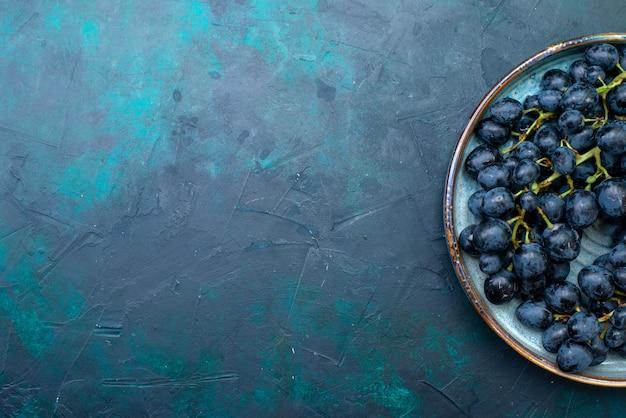 Bovenaanzicht donkere druiven in dienblad op donker