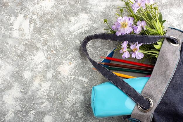 Bovenaanzicht donkere tas met voorbeeldenboeken en bloemen op wit oppervlak