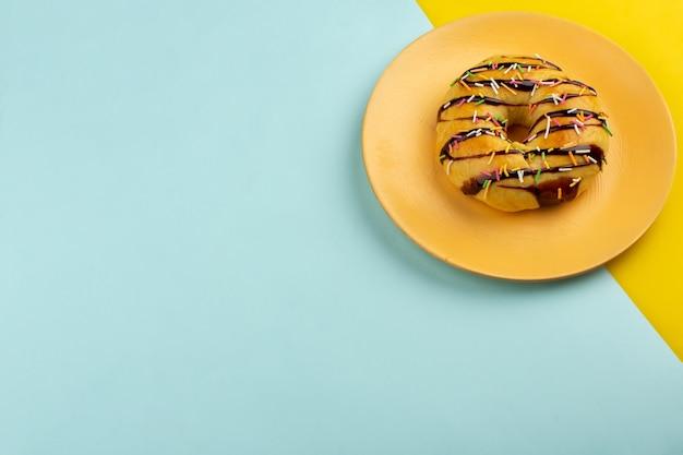 Bovenaanzicht donut in oranje plaat op de kleurrijke