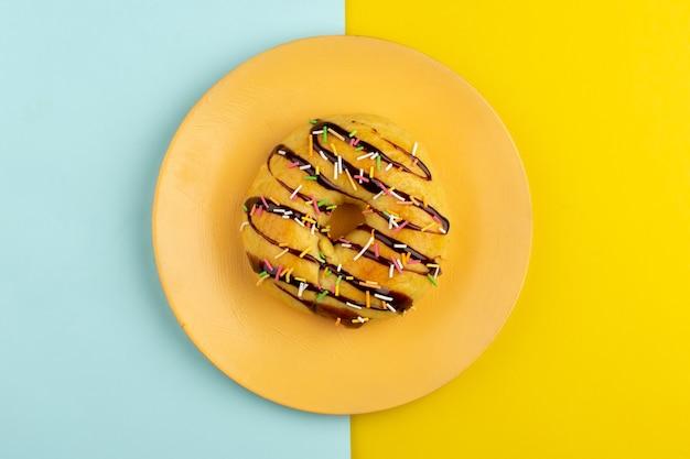 Bovenaanzicht donuts in oranje plaat op het blauw gele bureau