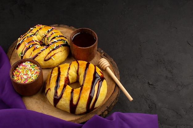 Bovenaanzicht donuts met heerlijke chocolade heerlijk op het bruine bureau en de grijze achtergrond