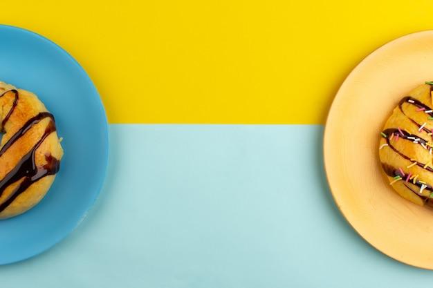 Bovenaanzicht donuts zoete lekkere binnenkant platen op de kleurrijke achtergrond