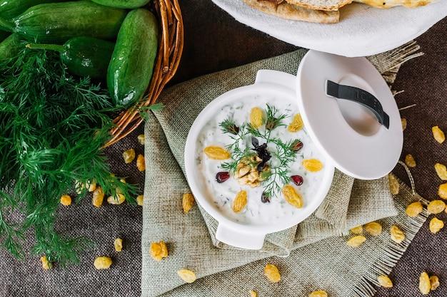 Bovenaanzicht dovga yoghurtsoep met dille en rozijnen
