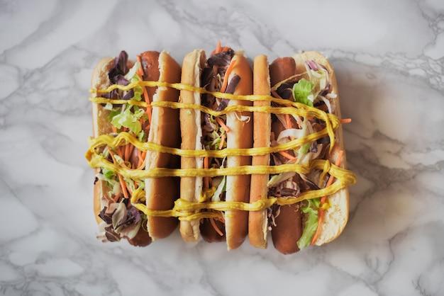Bovenaanzicht drie hotdogs met mosterd