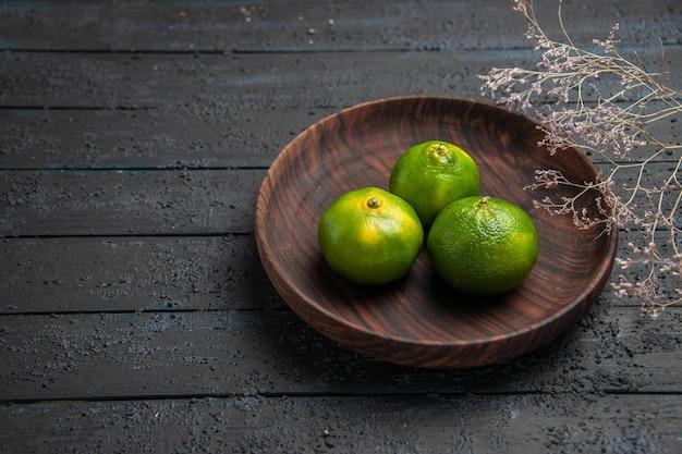Bovenaanzicht drie limoenen in kom drie groene limoenen in bruine kom naast de takken op de donkere tafel