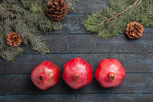 Bovenaanzicht drie rode granaatappels drie rijpe granaatappels naast sparren takken met kegels in het midden van de tafel