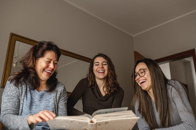 Bovenaanzicht drie vrouwen, moeder en dochters op zoek naar een boek met herinneringen en lachen. saamhorigheid, familieconcept.