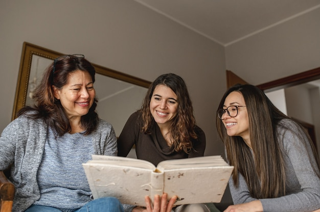 Bovenaanzicht drie vrouwen, moeder en dochters op zoek naar een boek met herinneringen. saamhorigheid, familieconcept.