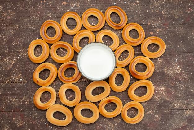 Bovenaanzicht drogen zoete ronde crackers samen met een glas koude melk op bruin, koekjeskoekje, zoete suiker knapperig