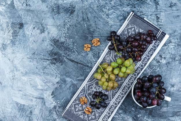 Bovenaanzicht druiven in witte kop met walnoten op grunge en keuken handdoek achtergrond. horizontaal