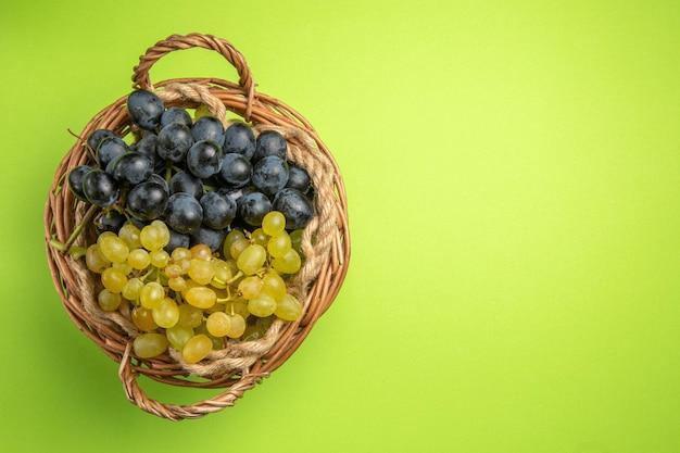 Bovenaanzicht druiventrossen druiven in de houten mand op de groene achtergrond