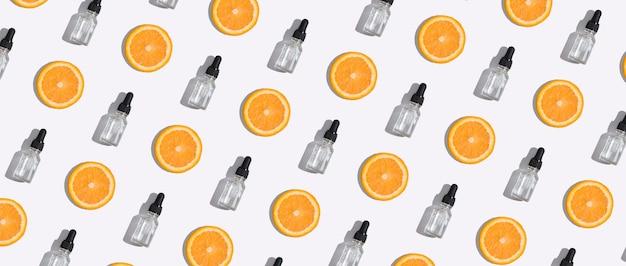 Bovenaanzicht druppelflesje vitamine c-serum, cosmetische olie en plakjes sinaasappel op witte achtergrond. creatief cosmeticapatroon in bannerformaat