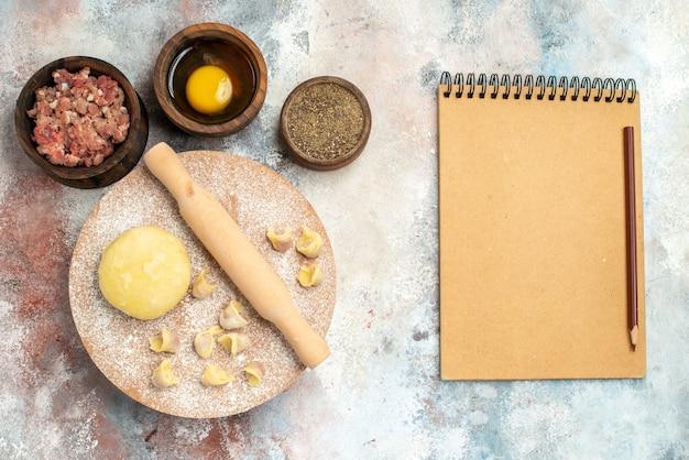 Bovenaanzicht dushbara deeg deegroller op deeg gebak bord kommen met vlees peper eidooier notebook potlood op naakt oppervlak