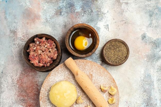 Bovenaanzicht dushbara deeg deegroller op deeg gebak bord kommen met vlees peper eigeel op naakt oppervlak vrije plaats