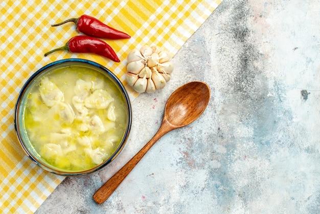 Bovenaanzicht dushbara dumplings soep in een kom hete pepers knoflook op gele en witte geruite keuken handdoek houten lepel op naakt oppervlak