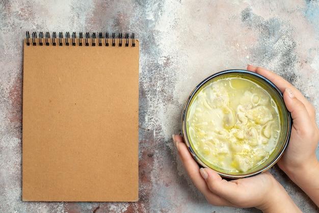 Bovenaanzicht dushbara dumplings soep in een kom in vrouwelijke hand een notitieboekje op naakt oppervlak