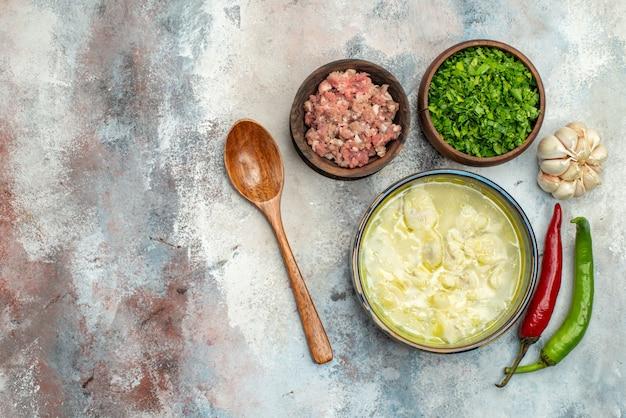 Bovenaanzicht dushbara dumplings soep in een kom knoflook hete pepers houten lepel kommen met vlees en greens op naakt oppervlak met kopie ruimte