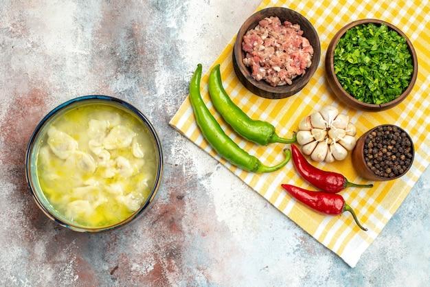 Bovenaanzicht dushbara dumplings soep in een kom knoflook hete pepers houten lepel kommen met vlees greens en zwarte peper op keukendoek op naakt oppervlak