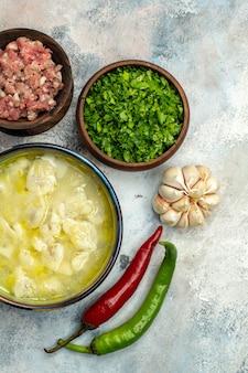 Bovenaanzicht dushbara dumplings soep in een kom knoflook hete pepers kommen met vlees en groenten op naakt oppervlak