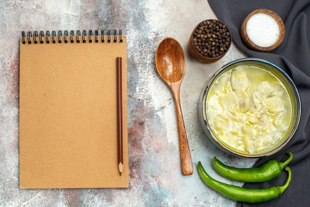 Bovenaanzicht dushbara een houten lepel zwarte keuken handdoek hete peper kommen met zwarte peper zout een potlood op notitieboekje op naakt oppervlak