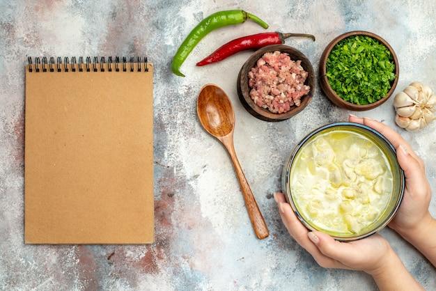 Bovenaanzicht dushbara knoedels soep in een kom in vrouw hand knoflook hete pepers houten lepel kommen met vlees en groenen een notitieblok op naakt oppervlak
