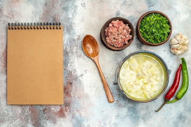 Bovenaanzicht dushbara knoedels soep in een kom knoflook hete pepers houten lepel kommen met vlees en greens een notitieboekje op naakt oppervlak