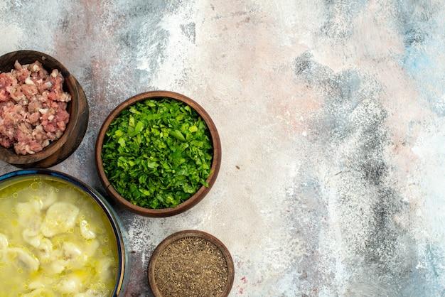 Bovenaanzicht dushbara knoedels soepkommen met vlees greens peper op naakt oppervlak vrije ruimte traditionele azerbeidzjaans gerecht