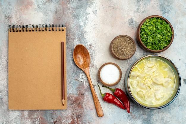Bovenaanzicht dushbara kommen met verschillende kruiden greens houten lepel een notebook potlood op naakt oppervlak