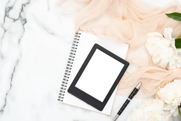 Bovenaanzicht e-book reader, papieren notitieblok, witte pioenrozen, pastel kleuren sjaal