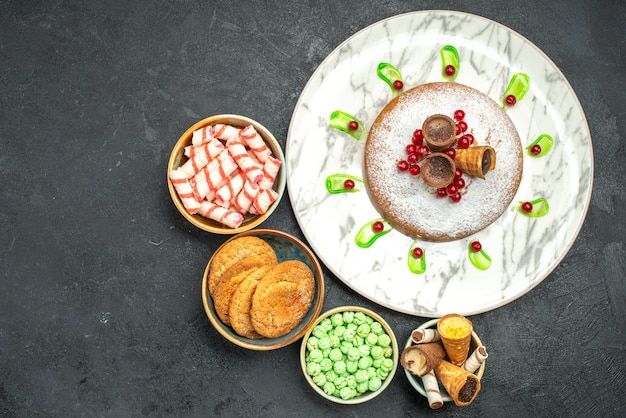 Bovenaanzicht een cake een cake met bessen chocoladewafels kommen met kleurrijke snoepjes
